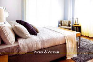 chambre appartement deux baies lit simple confort oreillers fauteuil table ronde Agence immobilière Victor & Victoire Real estate agency