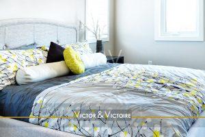 chambre confortable appartement lit double parure bleu blanc jaune Victor & Victoire immobilier Real Estate agency