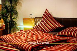 chambre oreillers rayés rouge chevet lumineux plante verte appartement Victor & Victoire immobilier