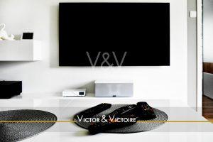 appartement bureau blanc noir écran tv mural télécommandes Victor & Victoire Immobilier Real estate agency